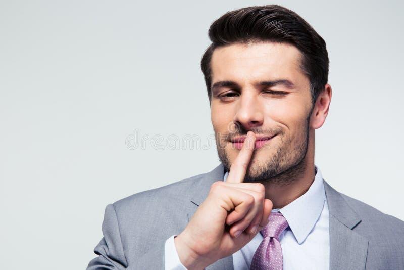 Uomo d'affari che indica dito sopra le labbra, chiedenti il silenzio fotografia stock libera da diritti