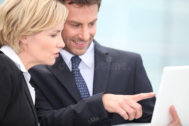 Uomo d'affari che indica il computer portatile fotografia stock