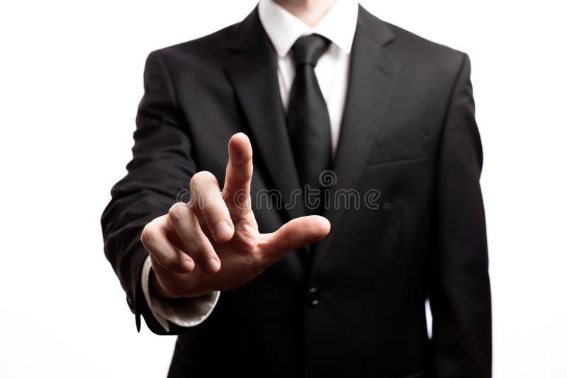 Uomo d'affari che indica il suo dito su un fondo bianco fotografie stock