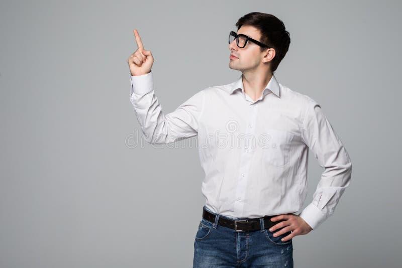 Uomo d'affari che indica lo spazio della copia Giovane felice in camicia che esamina macchina fotografica e che sorride mentre st fotografia stock