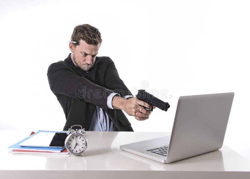 Uomo d'affari che indica pistola il computer nel concetto del lavoro straordinario e di lavoro eccessivo fotografia stock libera da diritti
