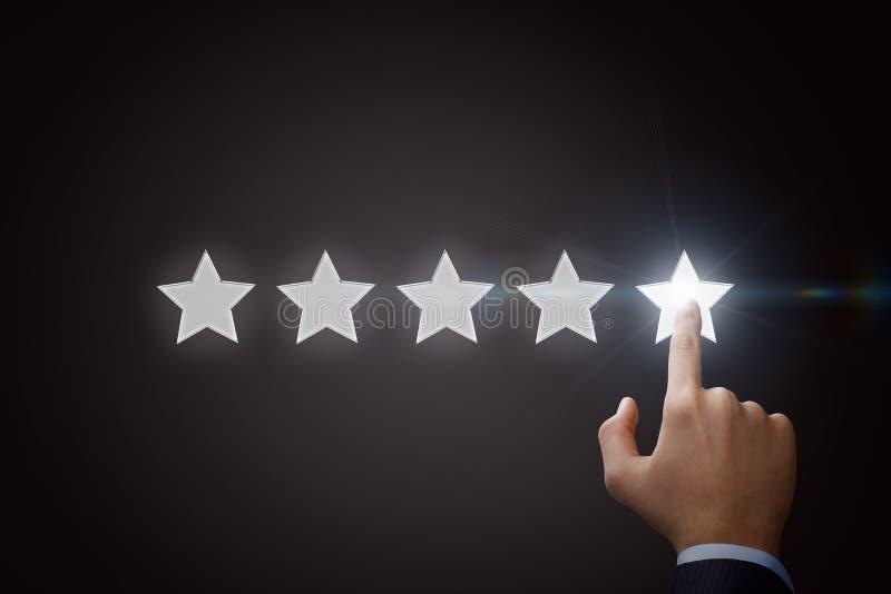 Uomo d'affari che indica stella cinque per aumentare la valutazione fotografie stock