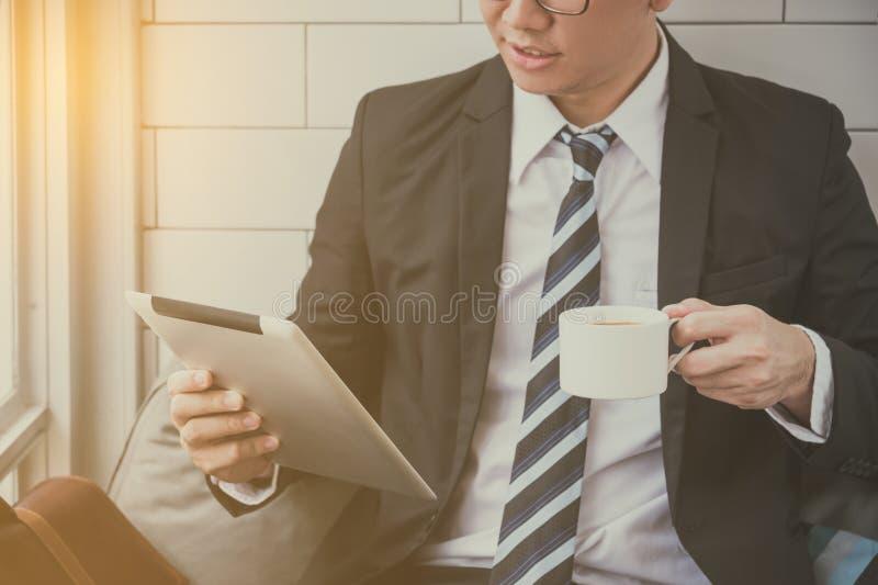 Uomo d'affari che indossa seduta del vestito e le notizie nere della lettura in compressa computern immagini stock