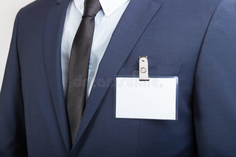 Uomo d'affari che indossa una carta in bianco dell'etichetta o di nome di identificazione durante un'esposizione o la conferenza fotografia stock libera da diritti