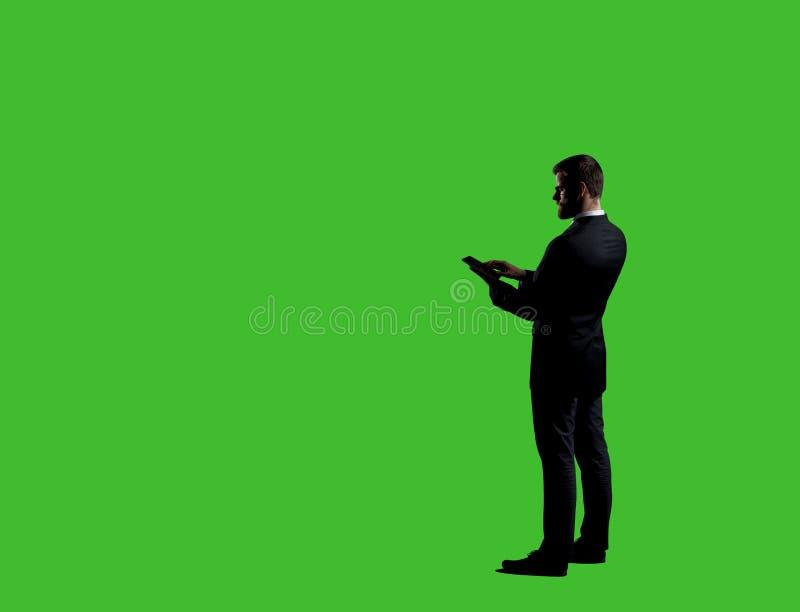 Uomo d'affari che invia gli sms con uno smartphone Fondo nero con fotografia stock