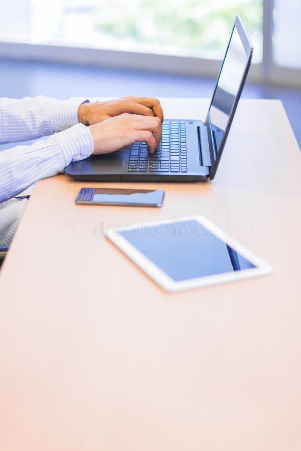 Uomo d'affari che lavora ad una tavola con alcuni apparecchi elettronici fotografia stock libera da diritti