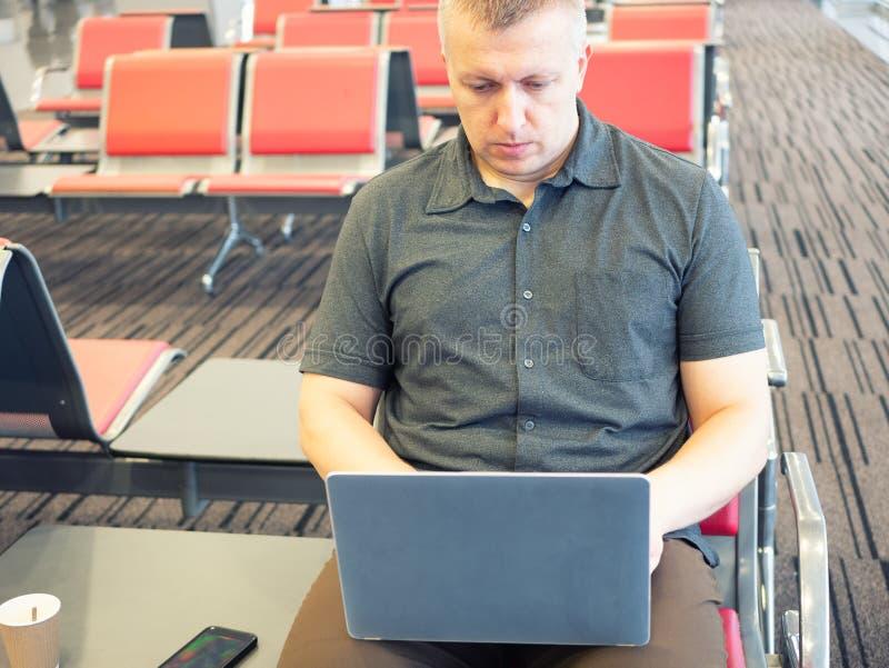 Uomo d'affari che lavora al computer portatile all'aeroporto immagini stock