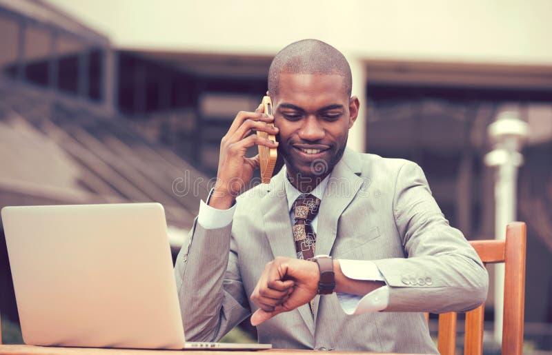 Uomo d'affari che lavora al computer portatile che parla sul telefono che esamina orologio immagini stock