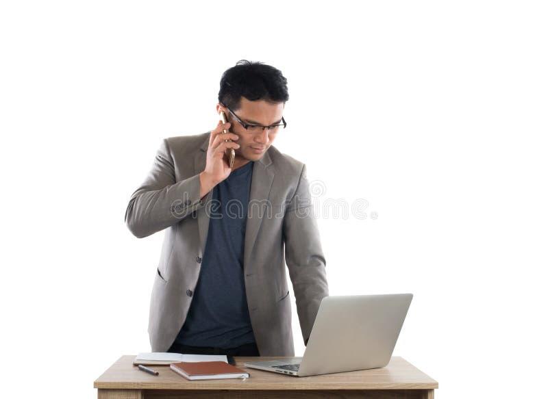 Uomo d'affari che lavora al computer portatile e che rivolge al telefono, backgr bianco fotografia stock