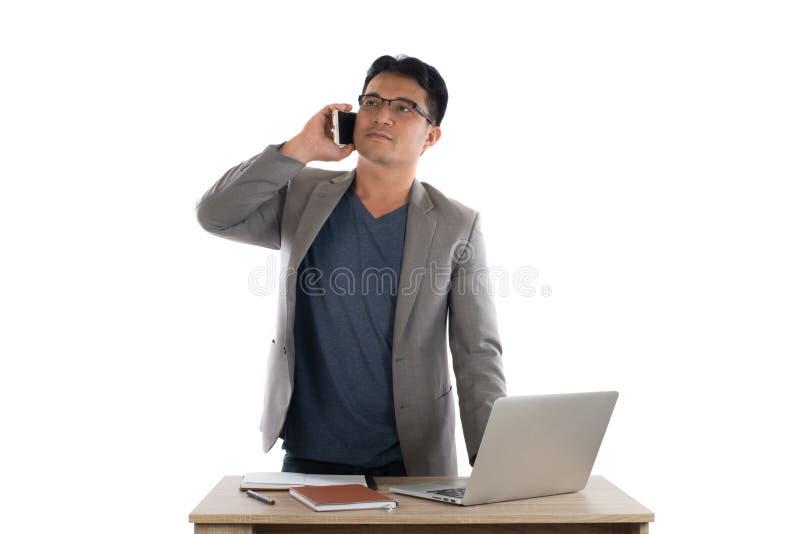 Uomo d'affari che lavora al computer portatile e che rivolge al telefono, backgr bianco fotografie stock libere da diritti