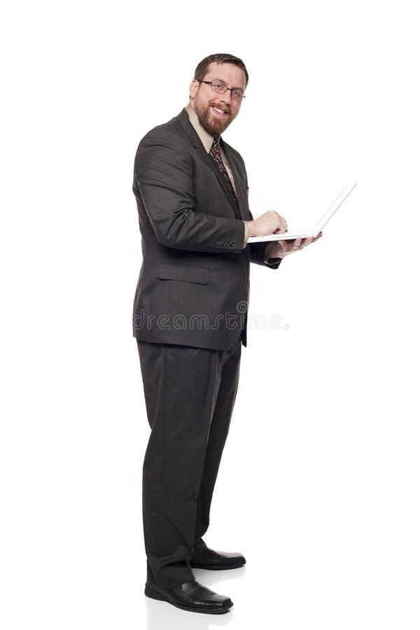 Uomo d'affari che lavora al computer portatile mentre levandosi in piedi immagini stock