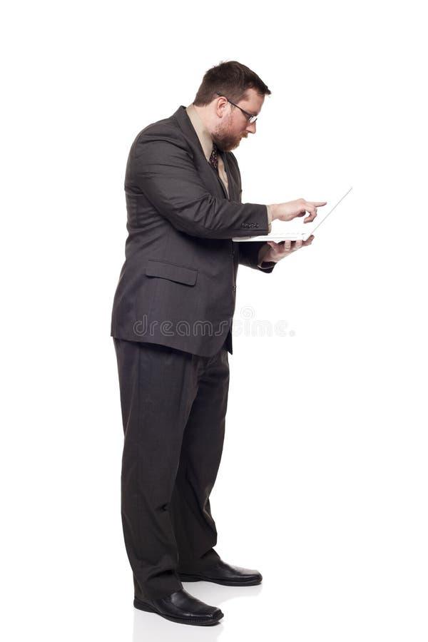 Uomo d'affari che lavora al computer portatile mentre levandosi in piedi immagine stock