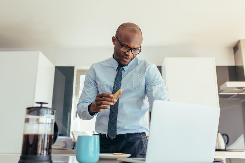 Uomo d'affari che lavora al computer portatile mentre mangiando prima colazione fotografia stock libera da diritti
