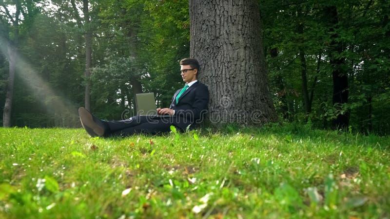 Uomo d'affari che lavora al computer portatile, sedendosi sull'erba in parco, routine d'evasione dell'ufficio fotografia stock