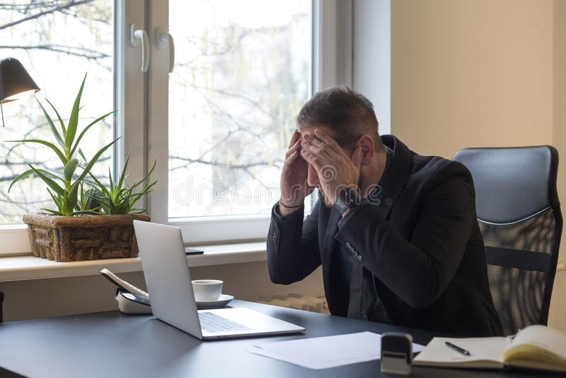 uomo d'affari che lavora al computer portatile in ufficio che rende telefonata nervosa ed arrabbiata fotografia stock libera da diritti