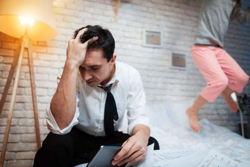 Uomo d'affari che lavora al ridurre in pani La bambina impedisce suo padre l'affare immagini stock