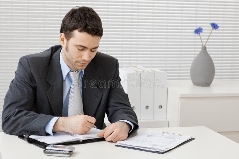 Uomo d'affari che lavora allo scrittorio fotografia stock