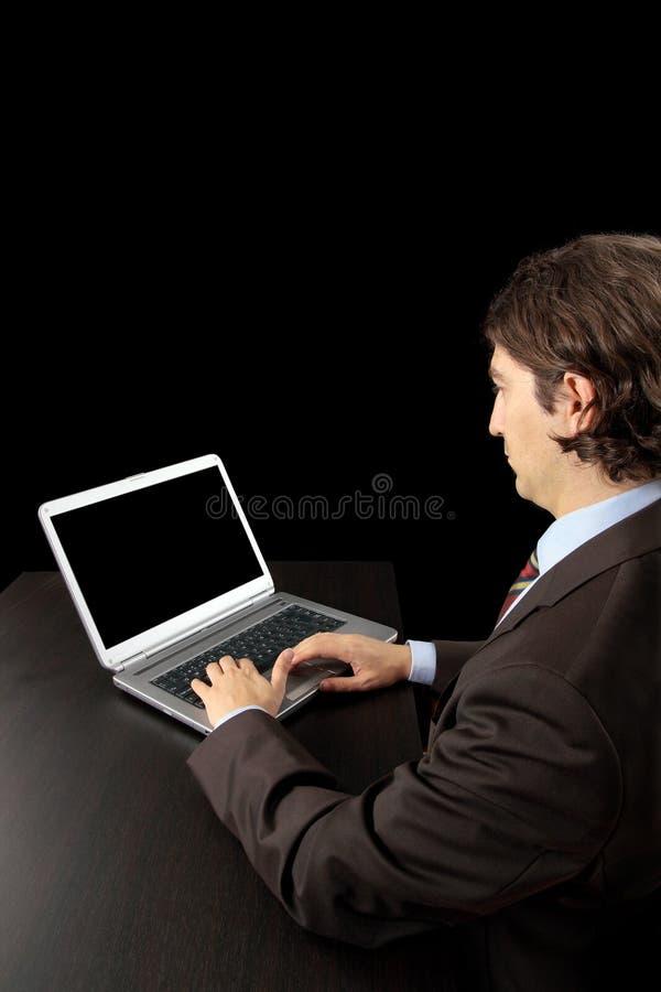 Uomo d'affari che lavora con il computer portatile immagine stock