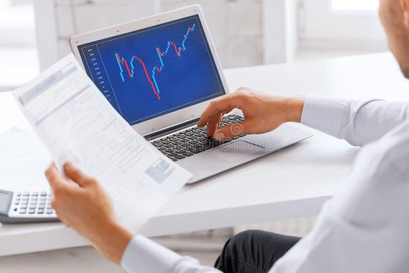Uomo d'affari che lavora con il grafico dei forex in ufficio immagini stock