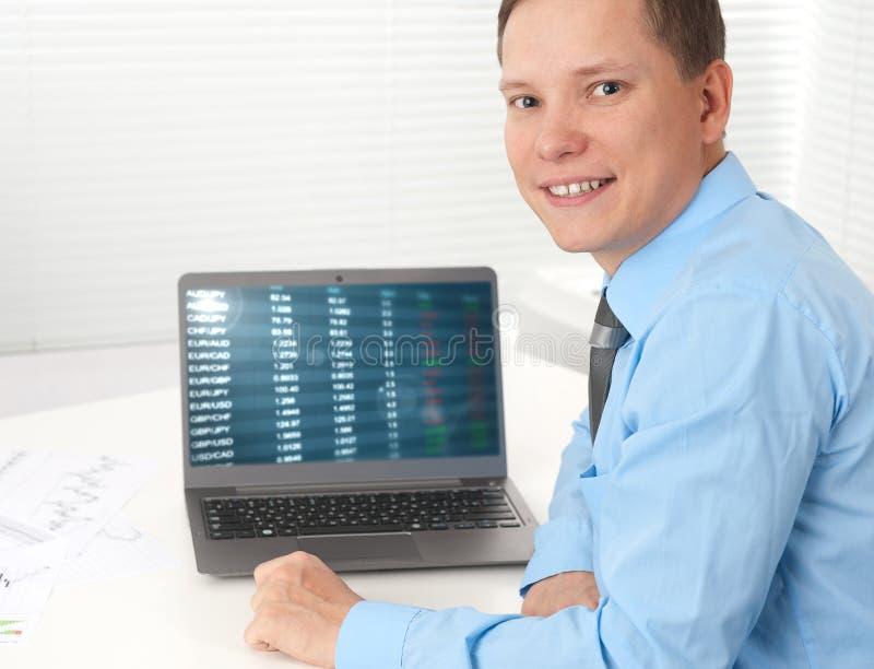 Uomo d'affari che lavora con il suo computer portatile allo scrittorio immagini stock