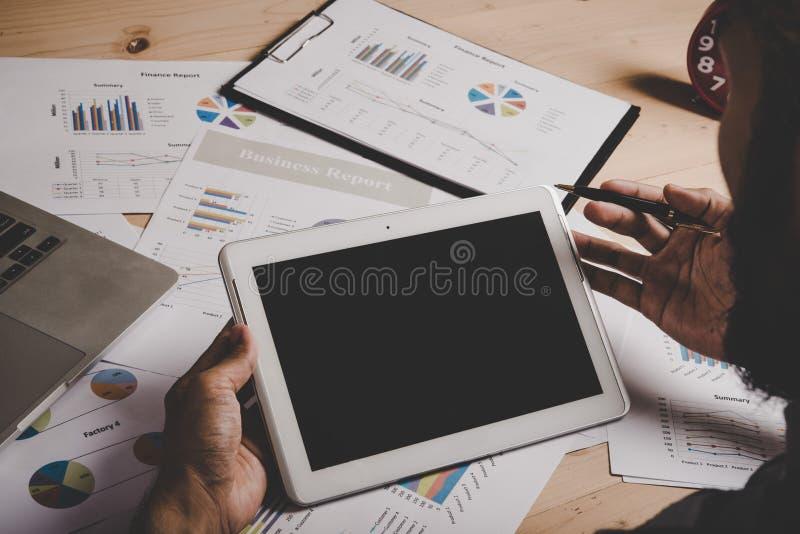 Uomo d'affari che lavora con la compressa digitale ed il computer portatile dello schermo in bianco immagini stock