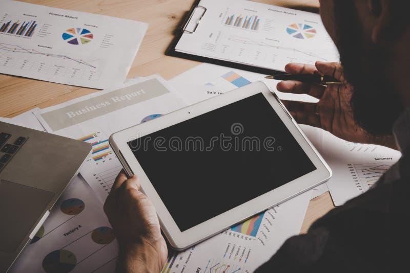 Uomo d'affari che lavora con la compressa digitale ed il computer portatile dello schermo in bianco immagine stock