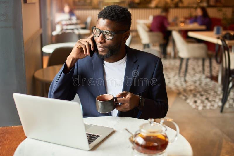Uomo d'affari che lavora dal caff? fotografie stock