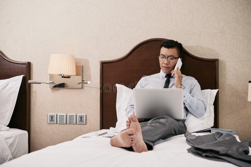 Uomo d'affari che lavora a letto fotografie stock libere da diritti