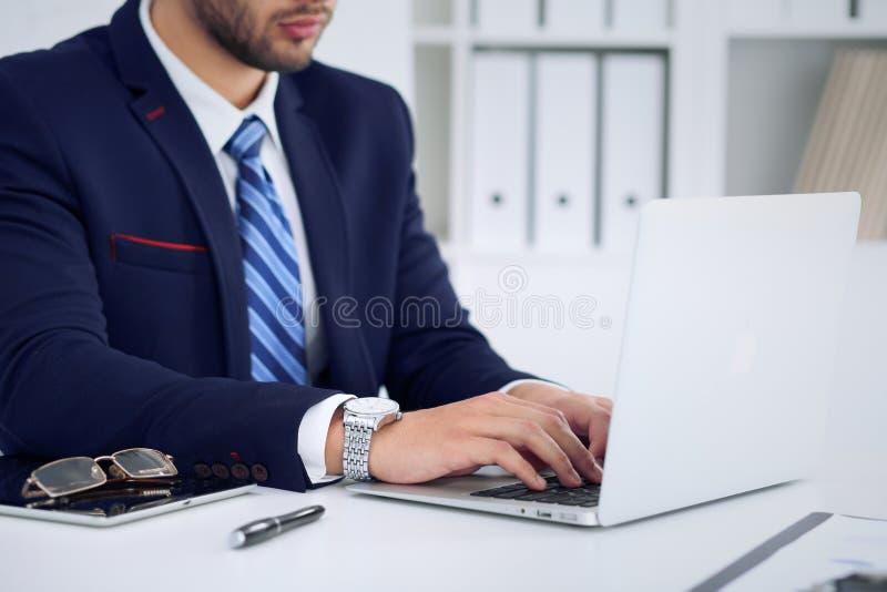 Uomo d'affari che lavora scrivendo sul computer portatile Equipaggi le mani del ` s sul taccuino o sull'uomo d'affari nel luogo d fotografia stock