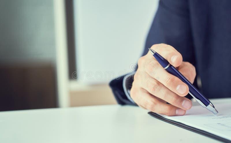 Uomo d'affari che legge contratto locativo prima della fabbricazione dell'affare Uomo corporativo con la penna a disposizione che immagine stock
