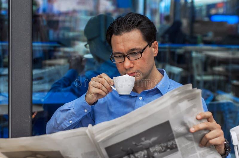 Uomo d'affari che legge un giornale mentre bevendo caffè Concetto di informazioni di Working Reading Newspaper dell'uomo d'affari fotografia stock