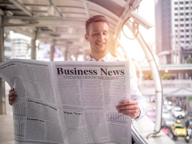 Uomo d'affari che legge un giornale sul modo lavorare in una mattina, buone notizie fotografia stock