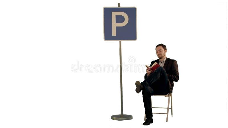Uomo d'affari che legge un libro vicino al segno di parcheggio sul fondo bianco isolato fotografia stock