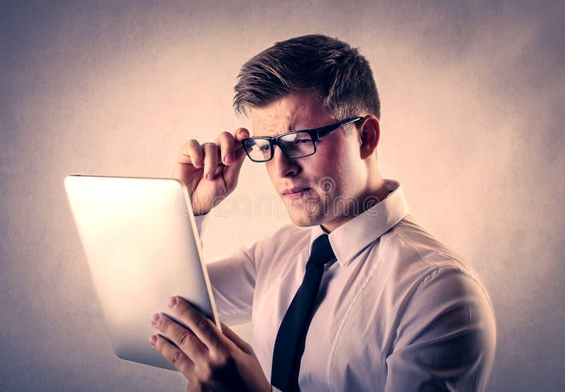 Uomo d'affari che legge un rapporto su una compressa immagine stock libera da diritti