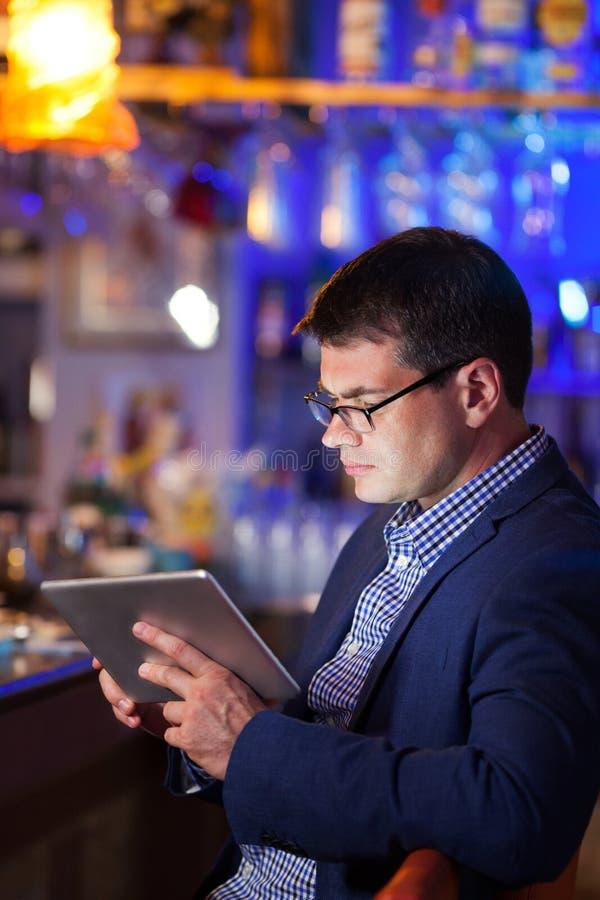 Uomo d'affari che legge una compressa in una barra del cocktail fotografie stock