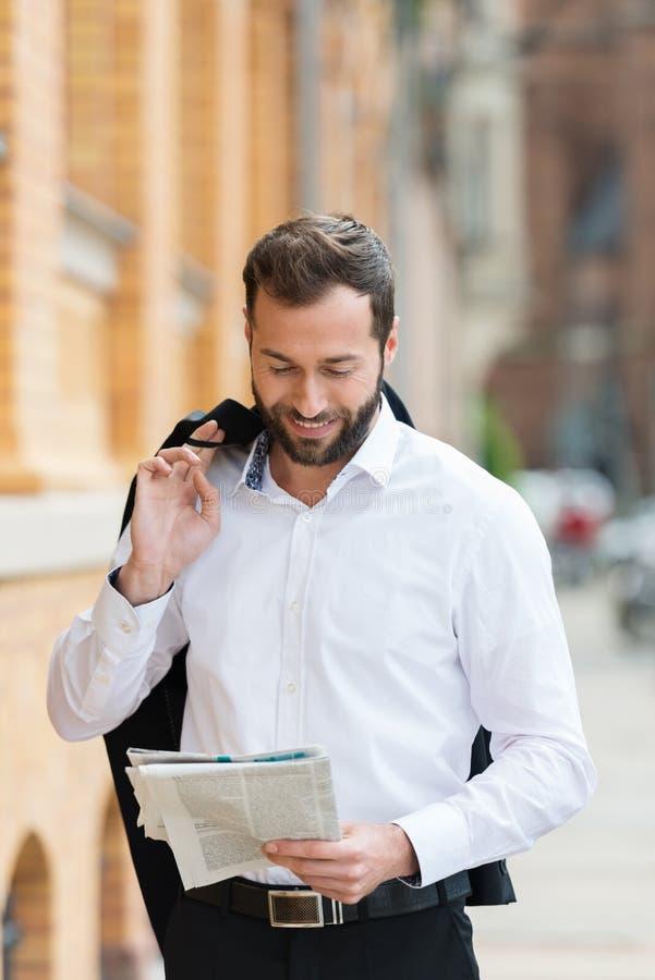 Uomo d'affari che legge una rivista durante la sua pausa immagine stock