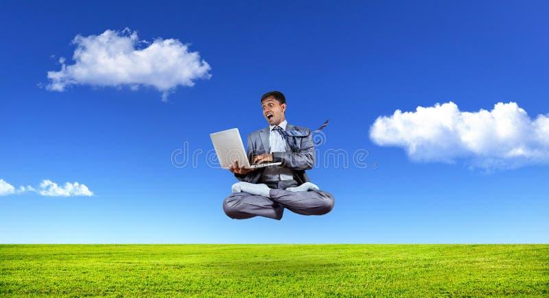 Uomo d'affari che levita con il computer portatile immagine stock libera da diritti