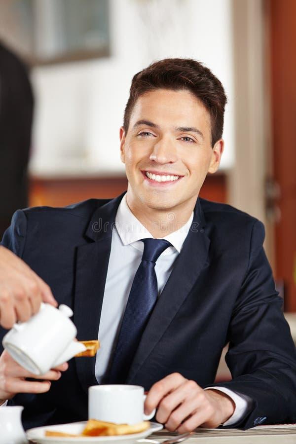 Uomo d'affari che mangia prima colazione in caffetteria immagini stock