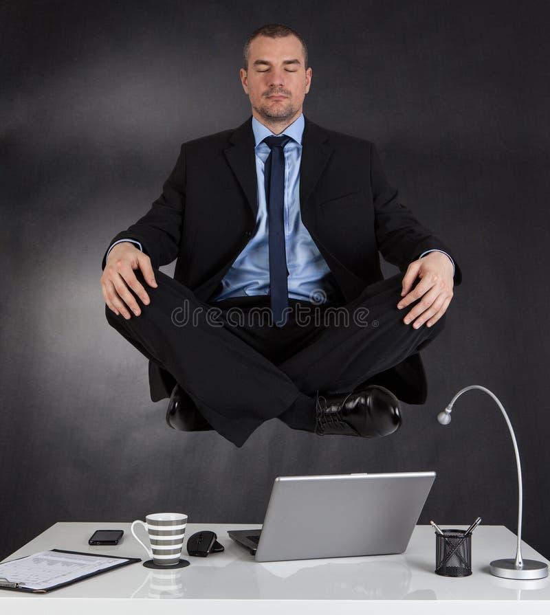 Uomo d'affari che medita nell'ufficio fotografia stock