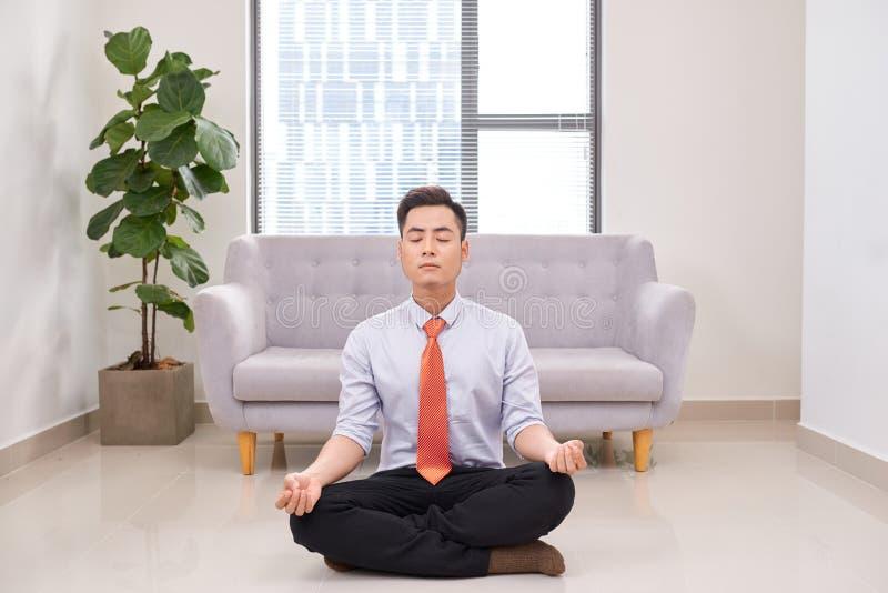 Uomo d'affari che medita nella posa del loto su pavimento nell'ufficio fotografia stock