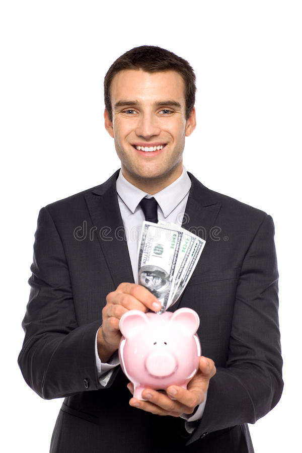 Uomo d'affari che mette soldi nella banca piggy fotografia stock libera da diritti