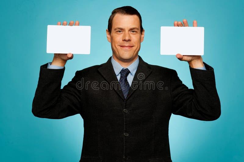 Uomo d'affari che mostra due cartelli bianchi in bianco fotografia stock