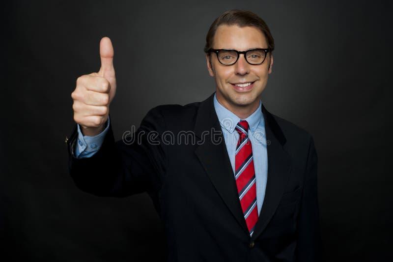 Uomo d'affari che mostra i pollici sul segno alla sua squadra fotografie stock