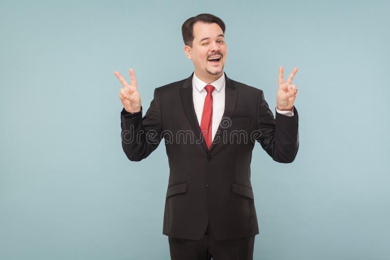 Uomo d'affari che mostra il nomber quattro del dito e strizzatina d'occhio fotografie stock libere da diritti