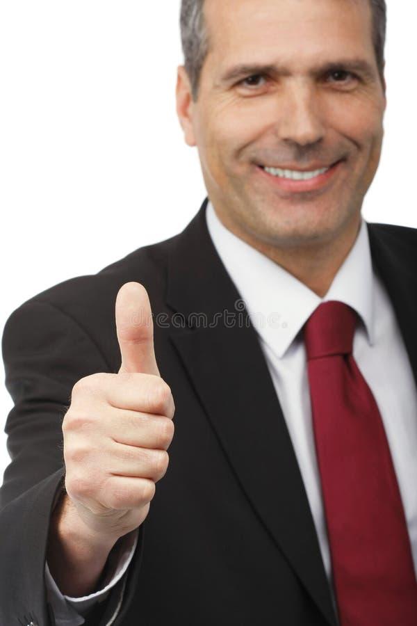 Uomo d'affari che mostra il segno di thumbs-up immagine stock