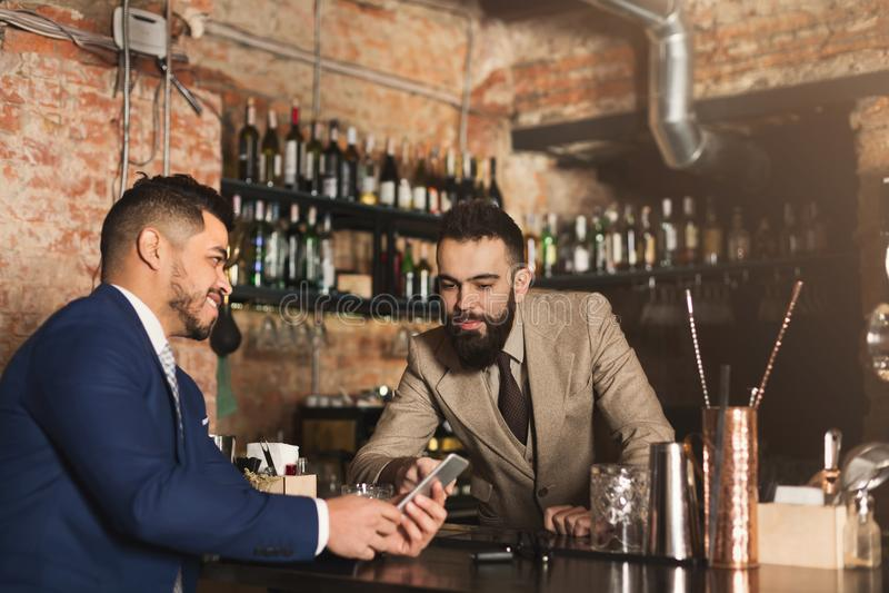 Uomo d'affari che mostra informazioni sul telefono al barista immagini stock