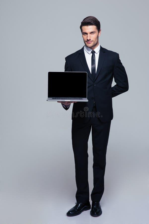 Uomo d'affari che mostra lo schermo in bianco del computer portatile fotografia stock
