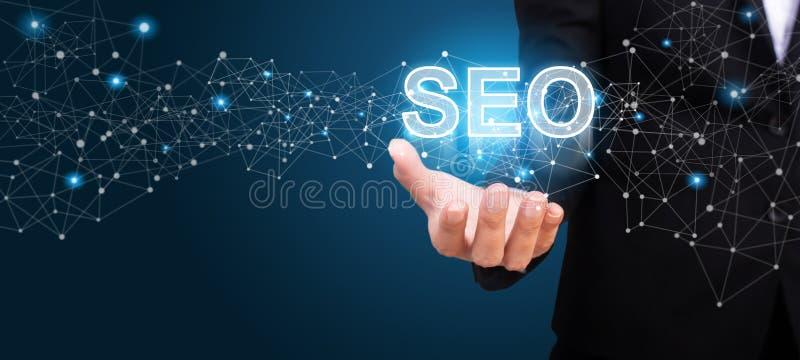 Uomo d'affari che mostra seo Il concetto dei siti Web d'ottimizzazione immagine stock