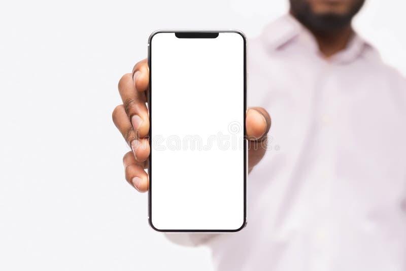 Uomo d'affari che mostra Smart Phone, con lo spazio della copia immagini stock