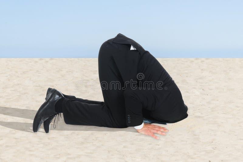 Uomo d'affari che nasconde il suo capo in sabbia fotografie stock